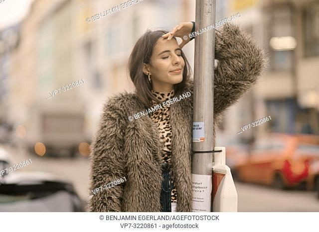 young woman with closed eyes leaning on traffic sign at street in city, relaxed mood, contemplating, in Munich, Germany