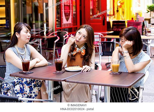 Business women eating a cake at an outdoor cafe