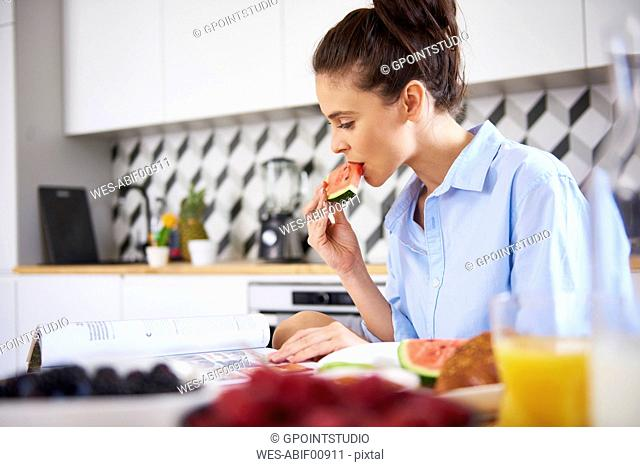 Young woman at home in kitchen, eating breakfast, reading book