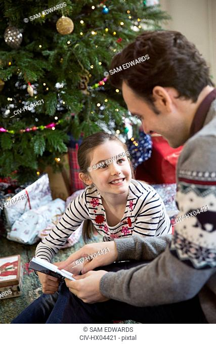 Father reading book with daughter at Christmas tree