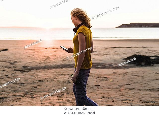 Teenage girl at the beach using smart phone