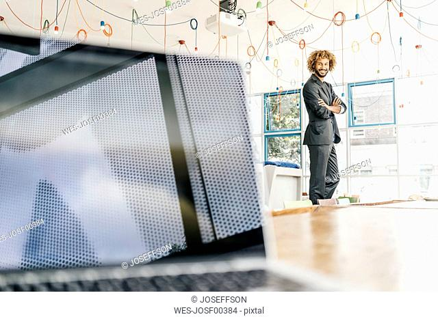 Young businessman standing at window