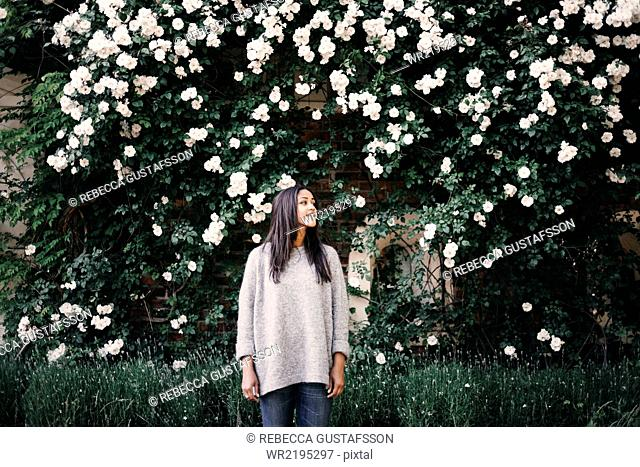 Young woman standing against tree bearing white flowers in park