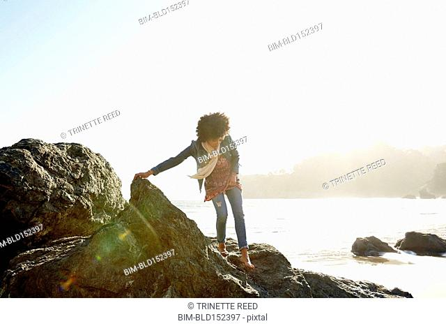 Mixed race woman climbing on boulders on beach