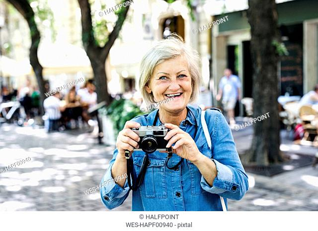 Portrait of smiling senior woman with camera