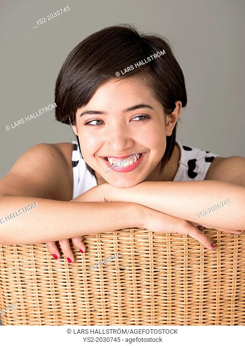 Young confident woman sitting in wicker chair looking away and smiling.	1015