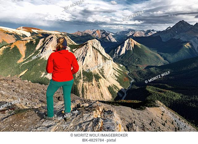 Female hiker looks from summit over mountain landscape, summit with orange Sulphur deposits, panoramic view, Sulphur Skyline Trail, Nikassin Range