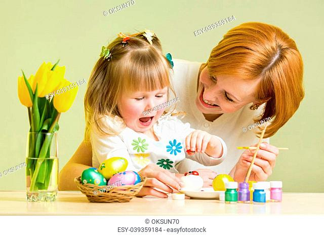 mother and kid girl play and prepare to easter