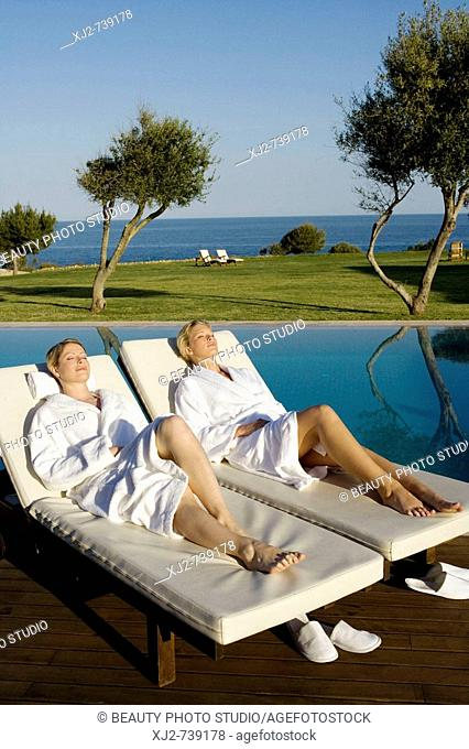 Two women relaxing on a sun lounger in a Hotel by the sea