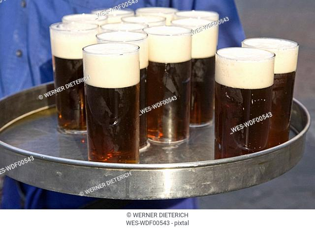 Germany, Waiter holding tray with beer glasses