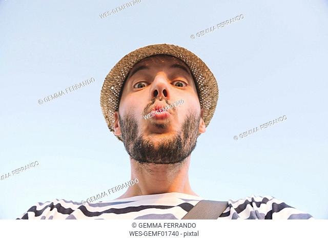 Man with straw hat kissing to the camera
