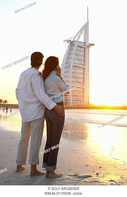 Couple admiring monument on beach, Dubai, United Arab Emirates
