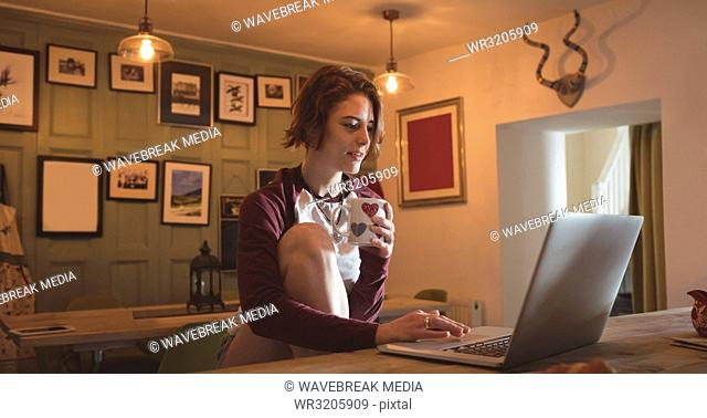 Woman using laptop while having coffee
