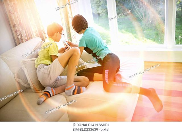 Mixed Race brother and sister texting on cell phone near window