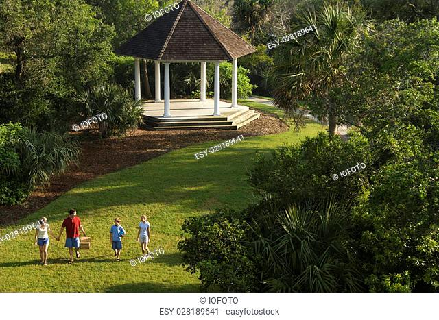 Caucasian family of four walking in park carrying picnic basket