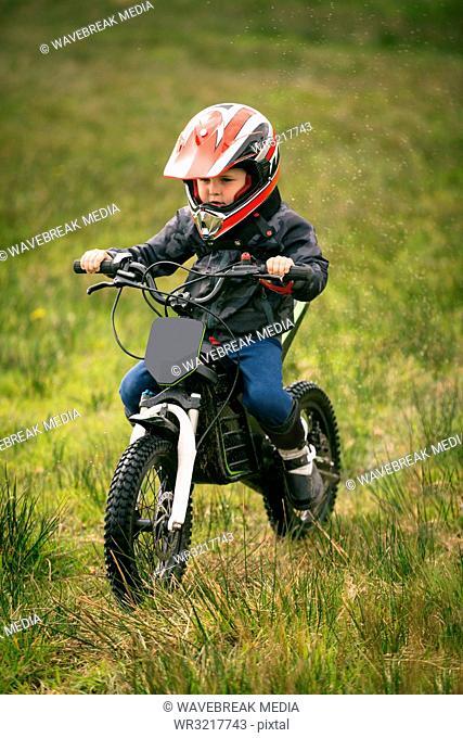 Kid rider riding a bike in garden
