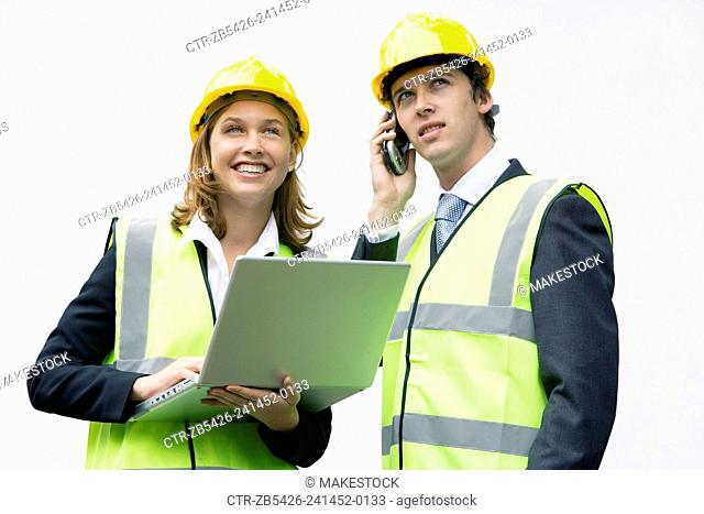 Team of young professionals on a construction site wearing hard hat and using laptop computer and mobile phone