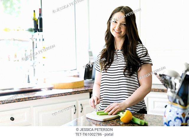 Woman cutting lemon and celery in kitchen