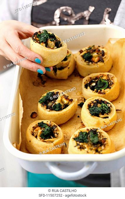 Pastries filled with spinach, ricotta and pine nuts in a roasting dish