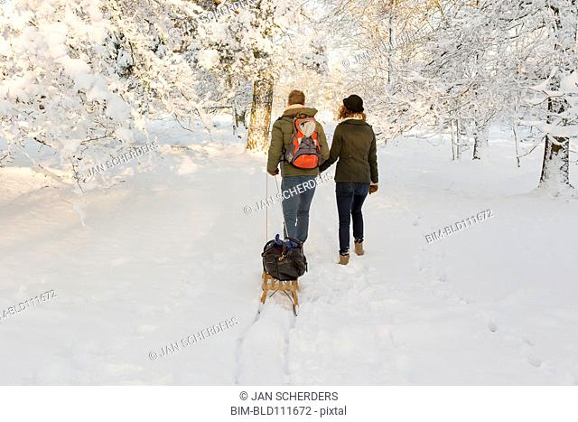 Caucasian couple pulling sled in snow