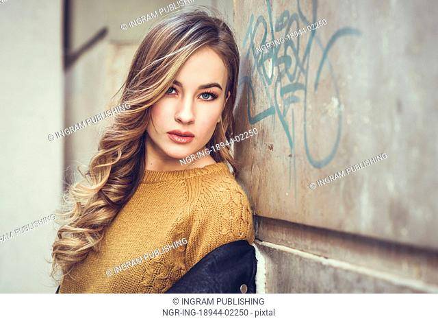 Blonde woman in urban background. Beautiful young girl wearing black leather jacket and mini skirt standing in the street