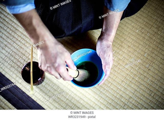 High angle close up of Japanese man wearing traditional kimono kneeling on floor using bamboo whisk to prepare Matcha tea in a blue bowl during tea ceremony