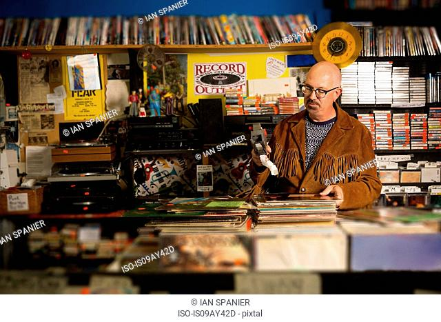 Mature man in record shop, pricing up records using price gun