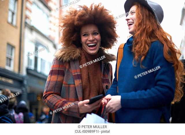 Two young women in street, laughing