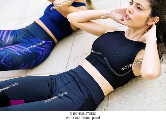 Two sportive young women doing sit-ups