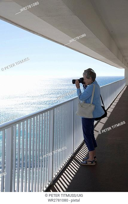 Woman taking a photo of the Gulf coastline from a high rise balcony