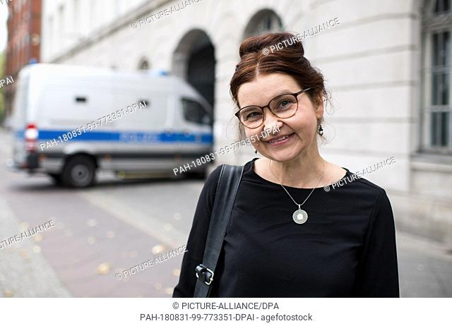 27 August 2018, Germany, Berlin: Justina Loos, German-Polish interpreter, stands in front of a police station in Prenzlauer Berg