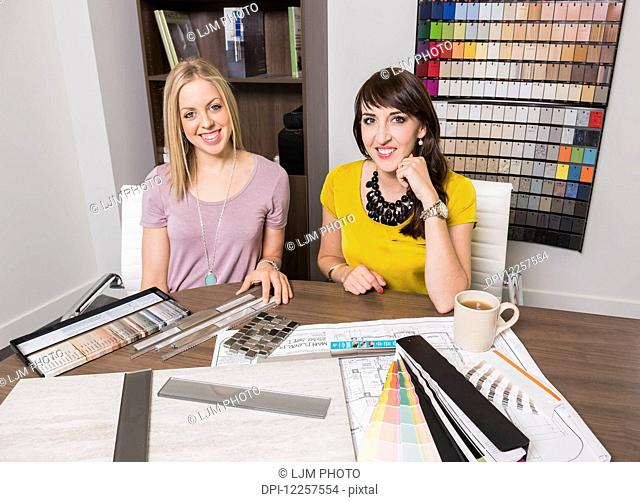 Design consultant and interior designer selecting paint and tile samples in a tile store; Edmonton, Alberta, Canada