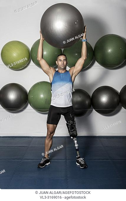 Adult confident sportsman with leg prosthesis holding medicine ball above head training in gym