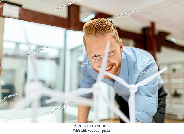 Businessman in office looking at models of wind turbines