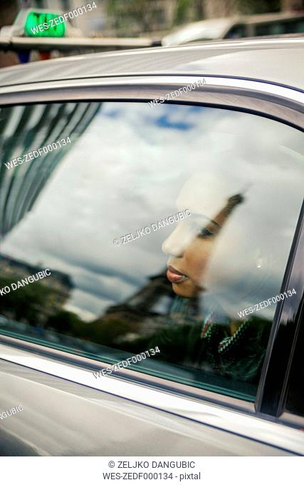 France, Paris, young woman looking through car window