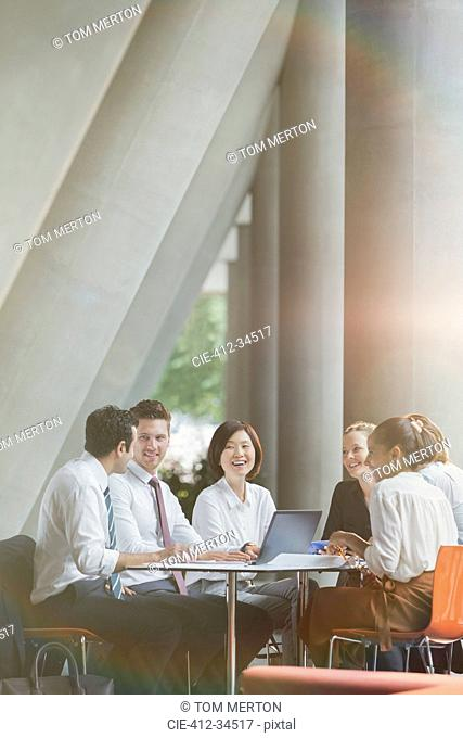 Smiling business people talking in conference room meeting