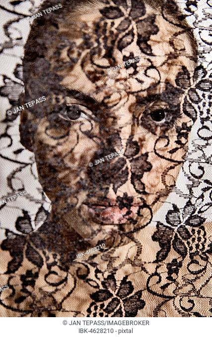 Face of a beautiful woman behind a transparent cloth with floral pattern, portrait, Germany