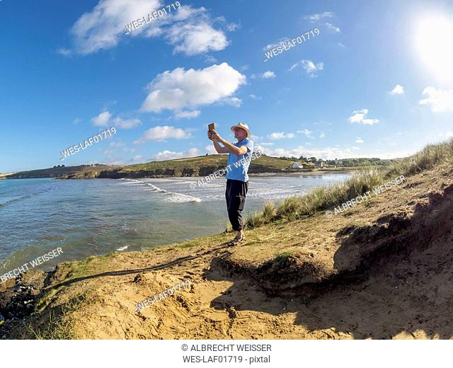 France, Brittany, Sainte-Anne-la-Palud, senior man with tablet at the beach Treguer plage