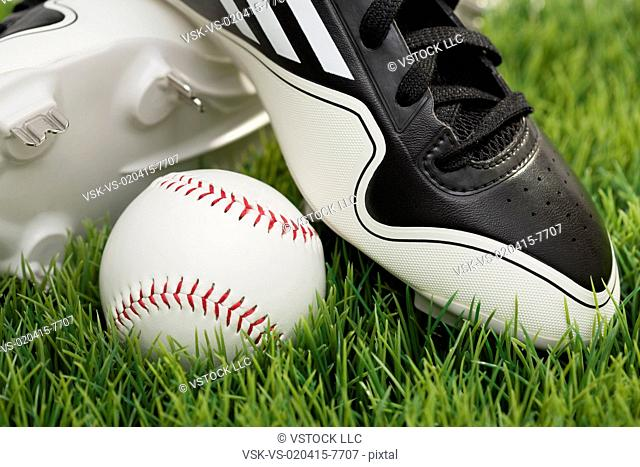 Baseball shoes and ball on grass