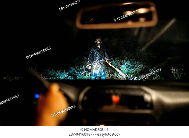 Serial maniac in hockey mask with bloody baseball bat wrapped in chain standing in the way of female victim on the car at the night. Horror, murderer