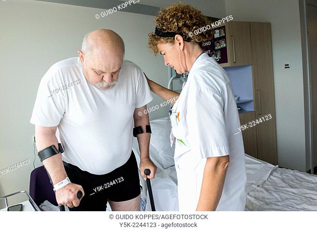 Tilburg, Netherlands. Physio therapist instructing a male post operative patient on how to walk again, after reviving a new hip in surgery
