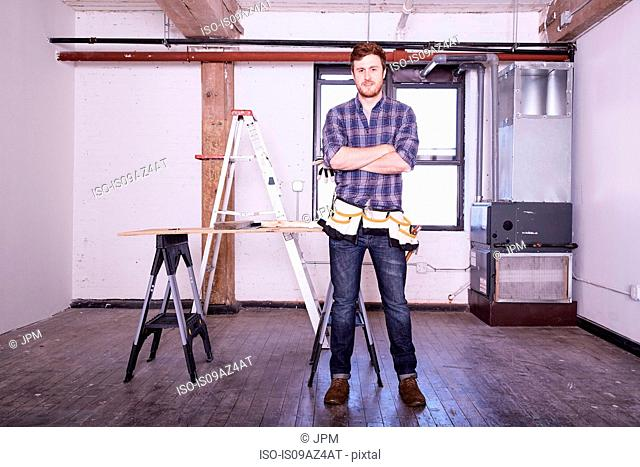 Young man in workshop wearing tool belt, arms crossed looking at camera