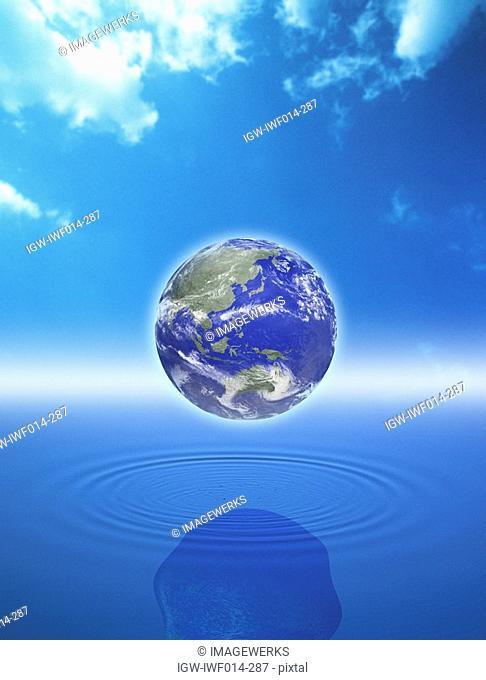 Digital composite of globe over water