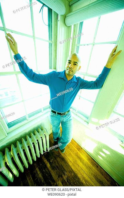 Young Hispanic man posing in front of several windows