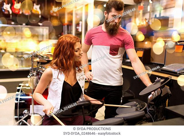 couple of musicians with drum kit at music store