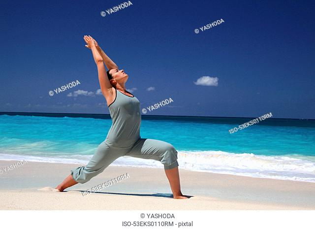 Woman practicing yoga on tropical beach