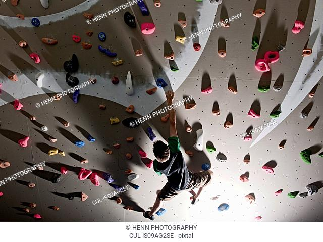 Mid adult man bouldering on climbing wall