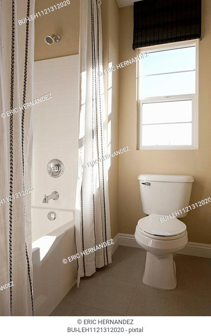 Toilet seat and shower room in bathroom; Murrieta; California; USA