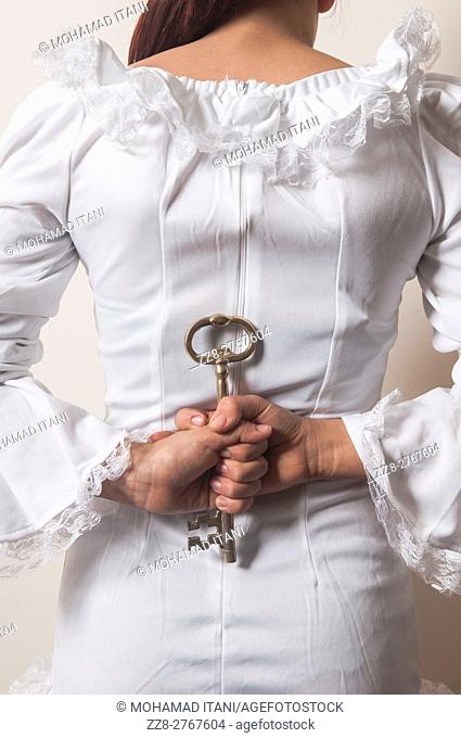 Woman holding a big key behind her back