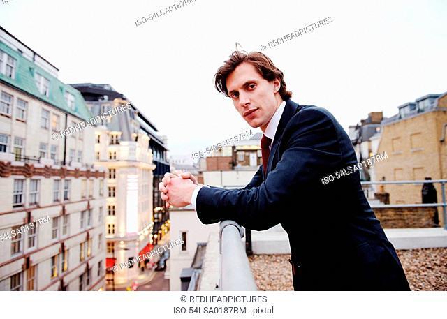 Businessman standing on urban rooftop